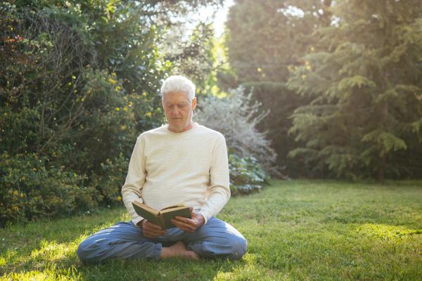 senior man reading a book in