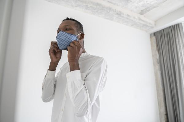man putting on reusable face mask