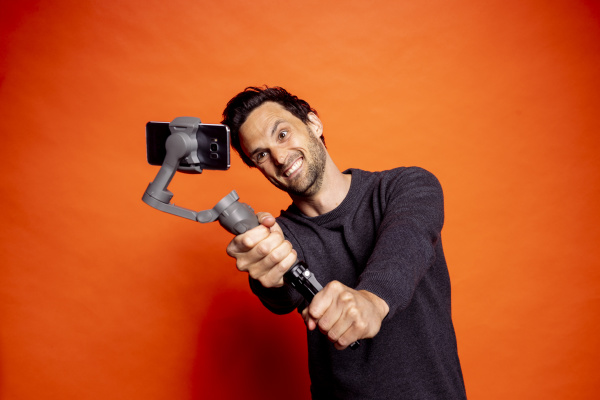 cheerful man taking selfie while holding