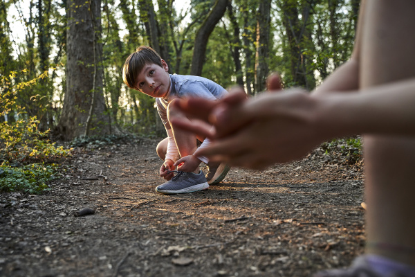 boy tying his shoelace while looking