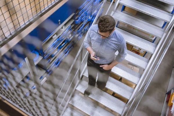 businessman using smartphone walking down stairs