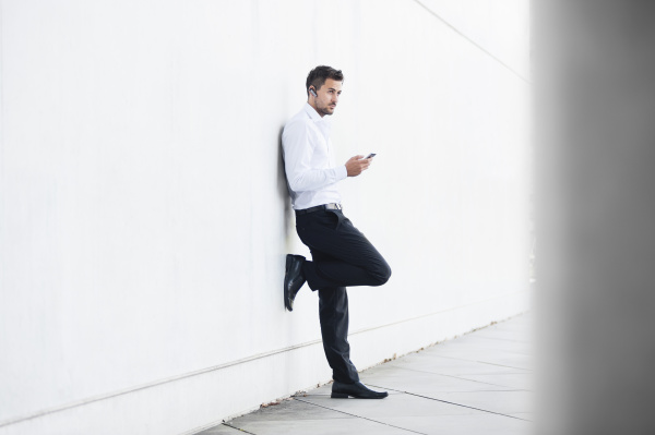 businessman using smartphone leaning on white