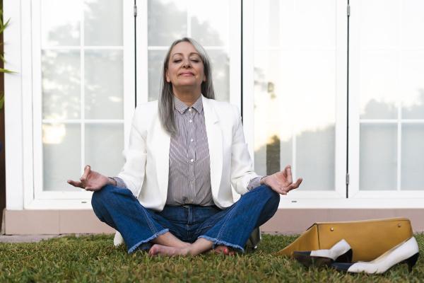senior businesswoman meditating while sitting in