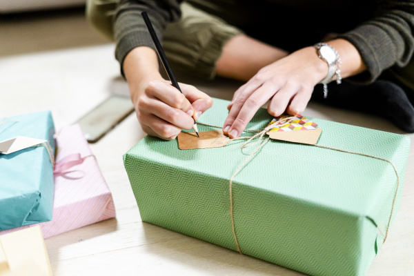 womans hands writing on present tag