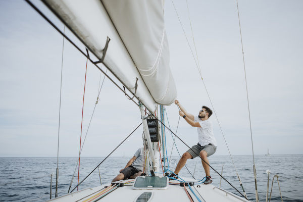 sailor maneuvering setting the mainsail in