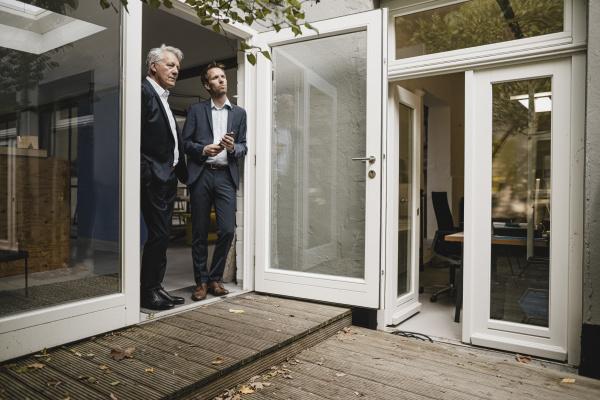 two businessmen leaning in office door