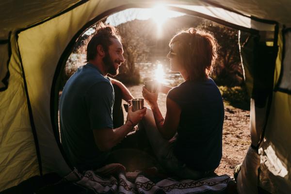 happy couple camping at lakeside