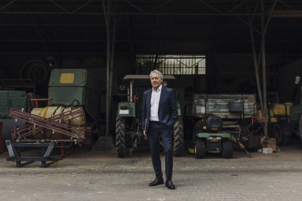 senior businessman standing on a farm