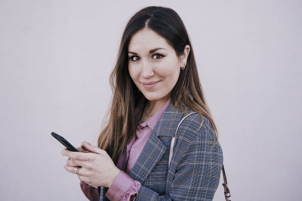 portrait of smiling woman using smartphone
