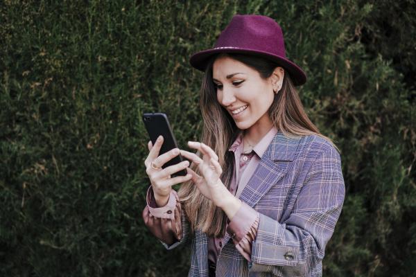 portrait of fashionable woman using smartphone