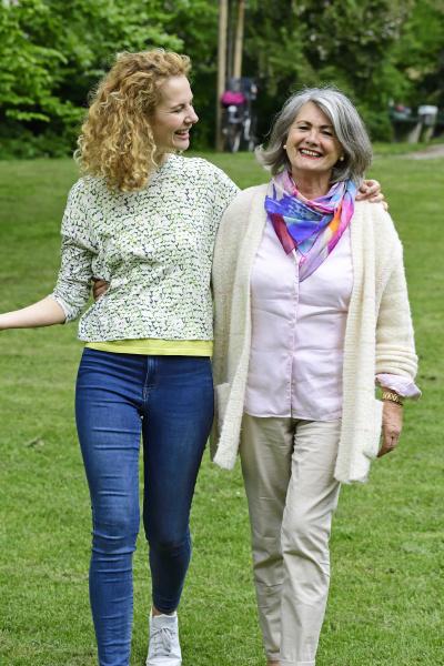 smiling senior woman walking with daughter