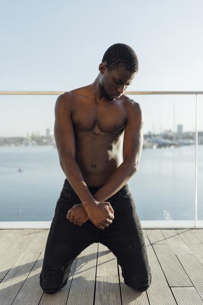 black man kneeling with crossed hands