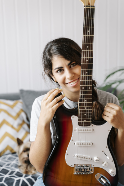 happy woman holding electric guitar while