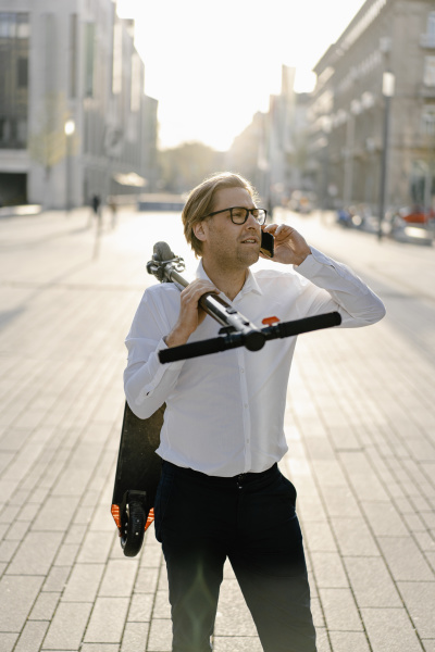 businessman with kick scooter on the