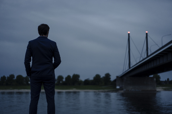 mature businessman standing at the riverbank