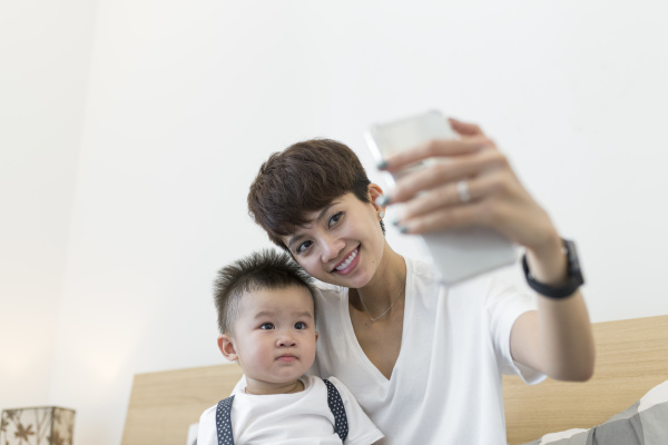 smiling mother taking selfie with cute