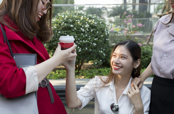 smiling young woman giving coffee to