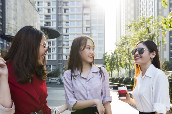 female friends talking while standing against