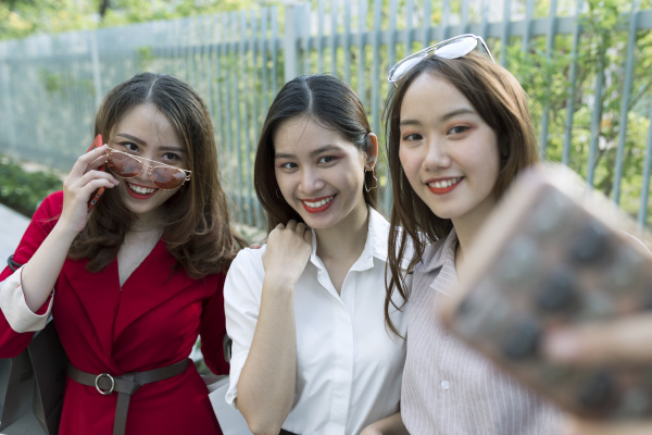 smiling woman taking selfie with friends