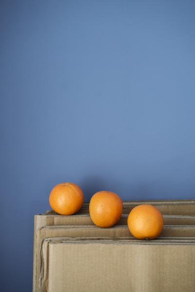 three oranges on cardboard against blue