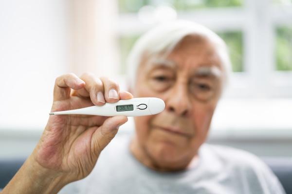ill sick senior man showing temperature