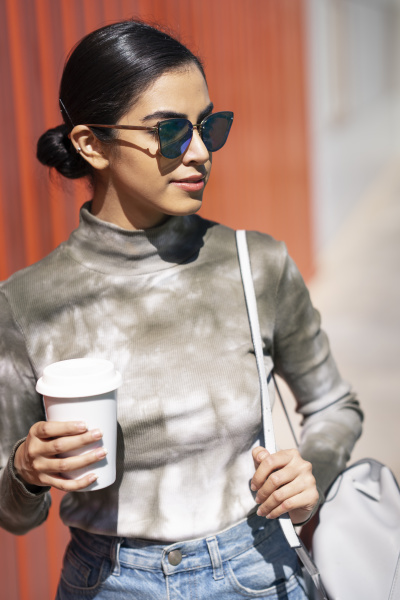 fashionable young woman holding coffee cup