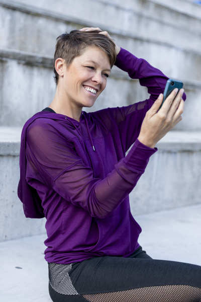 athletic woman using smartphone and taking