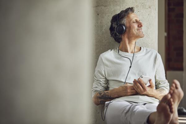 senior man with headphones listening music