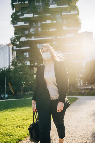 female business professional wearing mask walking