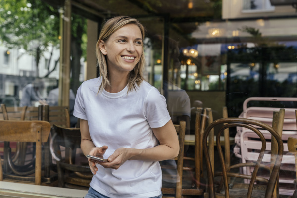 portrait of smiling woman with smartphone