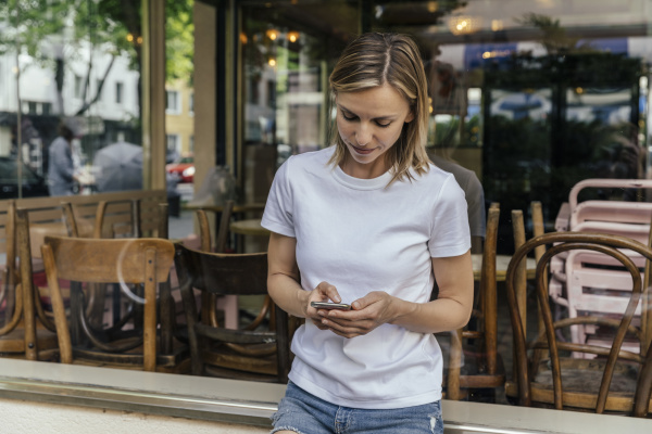 portrait of woman text messaging in