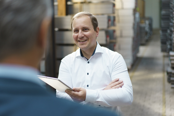 smiling businessman looking at colleague in