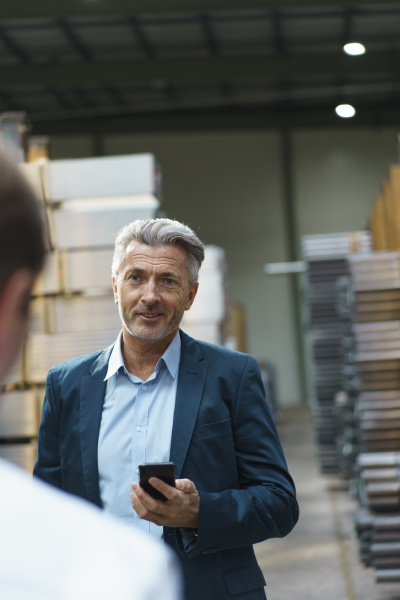 businessman holding mobile phone looking at