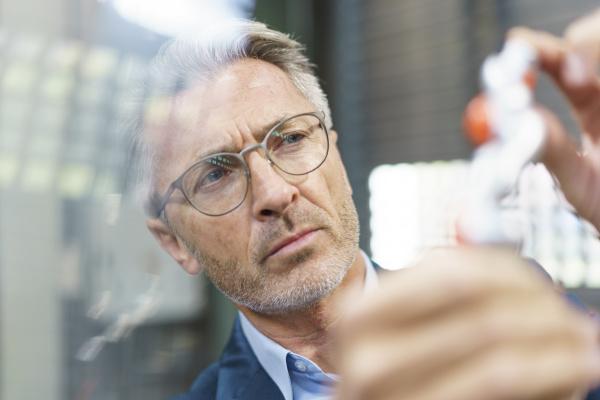 portrait of mature businessman examining industrial