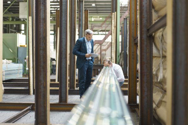 two businessmen examining steel pipes in