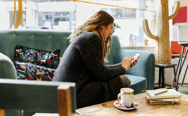 laughing woman using smartphone sitting on