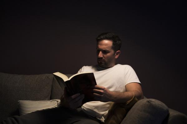 mature man reading book while sitting