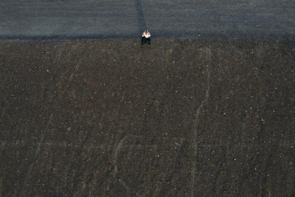 male entrepreneur sitting on hill drone