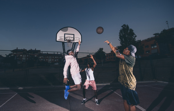 male friends playing basketball in court