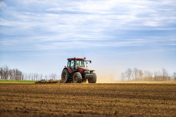farmer in tractor plowing field in