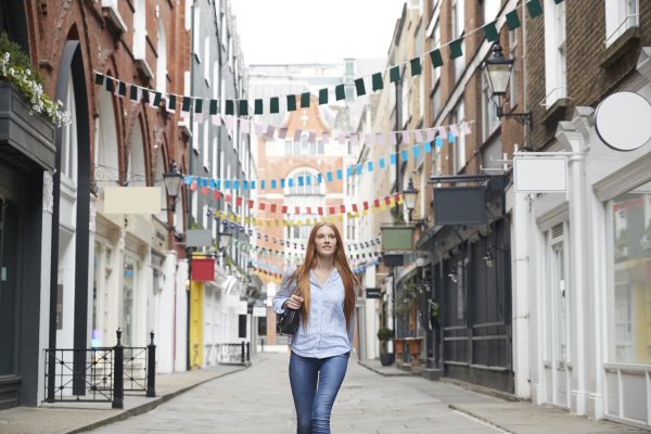 beautiful redhead woman walking on alley