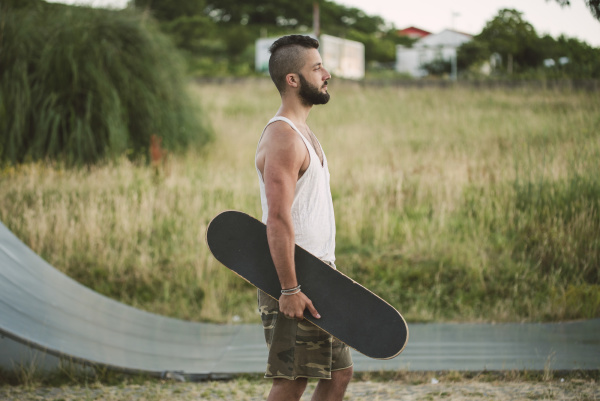 handsome young man holding skateboard looking