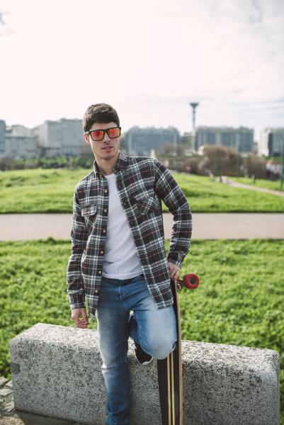 man wearing sunglasses holding skateboard while
