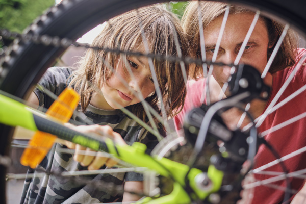father and son repairing bicycle during