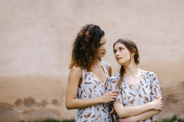 loving sisters wearing dresses looking at