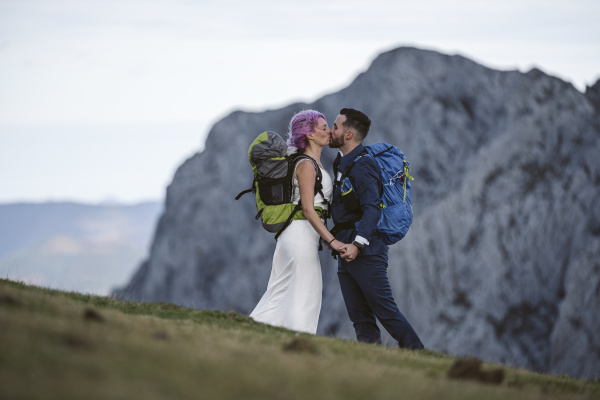 kissing bridal couple with climbing backpacks
