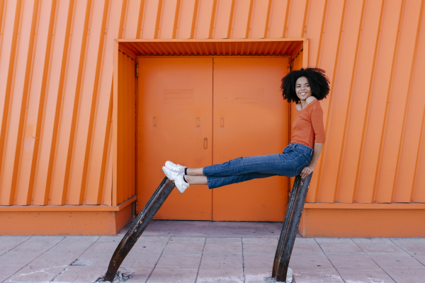 smiling young afro woman sitting on