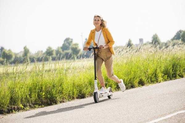 playful mature woman riding electric push