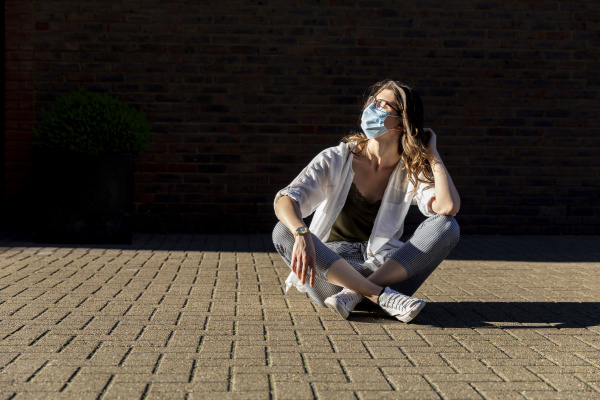 young woman wearing protective mask sitting