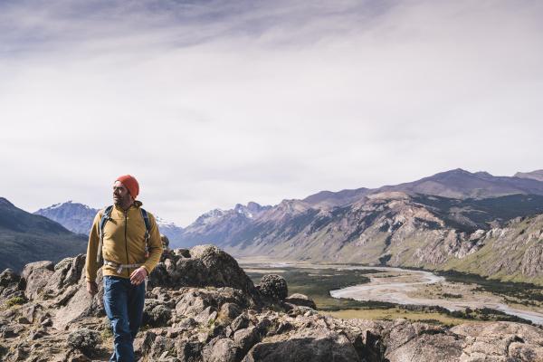 male hiker walking on rocks against